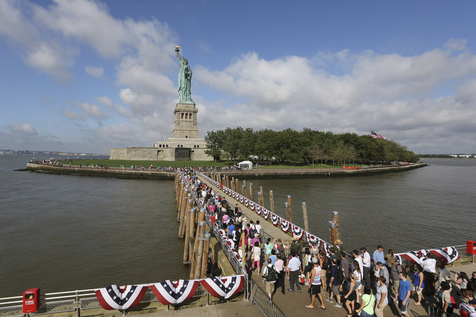 Photo - Visitors to the Statue of Liberty disembark onto Liberty Island from the first ferry to leave Manhattan, Thursday, July 4, 2013, in New York. The Statue of Liberty finally reopened on the Fourth of July months after Superstorm Sandy swamped its little island in New York Harbor as Americans across the country marked the holiday with fireworks and barbecues. (AP Photo/Mary Altaffer)