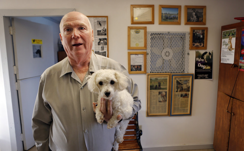 Photo - Inmate dog trainer Bill Miller works with maltese/poodle mix Jesse on Thursday, Jan. 29, 2015 at the Lexington Assessment and Reception Center in Lexington, Okla.    Photo by Steve Sisney, The Oklahoman