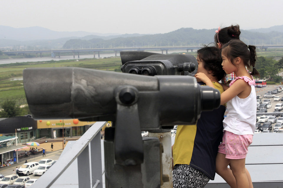 Photo - A family member uses binoculars to watch toward North Korea at the Imjingak Pavilion near the border village of Panmunjom which has separated the two Koreas since the Korean War, in Paju, South Korea, Saturday, June 7, 2014. North Korea has detained a 56-year old man from Ohio, accusing him of an unspecified crime after he traveled to the communist-led country as a tourist, the nation's state news agency and the man's family said Friday. (AP Photo/Ahn Young-joon)