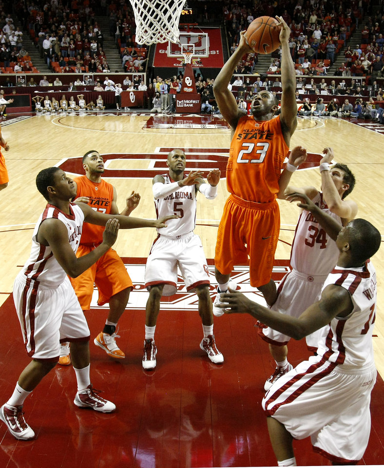 Photo - OSU's James Anderson (23) puts up a shot over the OU defense during the second half of the college bedlam basketball game between The University of Oklahoma Sooners (OU) and Oklahoma State University University Cowboys (OSU) at the Lloyd Noble Center on Monday, Jan. 11, 2010, in Norman, Okla.