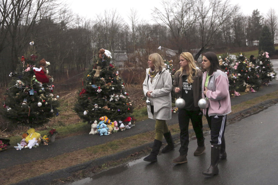 Photo - Mourners carry ornaments to decorate the Christmas trees at one of the makeshift memorials for the Sandy Hook Elementary School shooting victims, Monday,Dec. 17, 2012 in Newtown, Conn. Authorities say gunman Adam Lanza killed his mother at their home on Friday and then opened fire inside the Sandy Hook Elementary School in Newtown, killing 26 people, including 20 children, before taking his own life. (AP Photo/Mary Altaffer) ORG XMIT: CTMA106