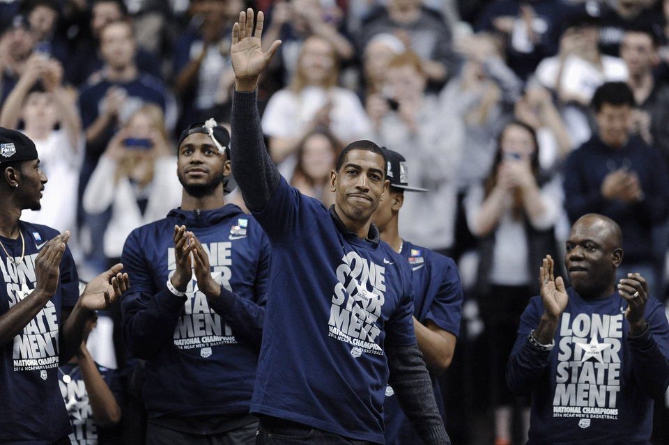 Photo - Connecticut coach Kevin Ollie waves to fans at a pep rally Tuesday, April 8, 2014, in Storrs, Conn., the day after the team won the NCAA men's Division I basketball championship. (AP Photo/Jessica Hill)