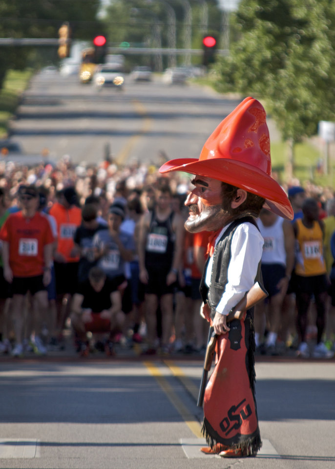 Pistol Pete stands in front of the runners before firing the starter gun to start the Remember the Ten run held in Stillwater, Okla., on April 21, 2012. Photo by Mitchell Alcala, for The Oklahoman