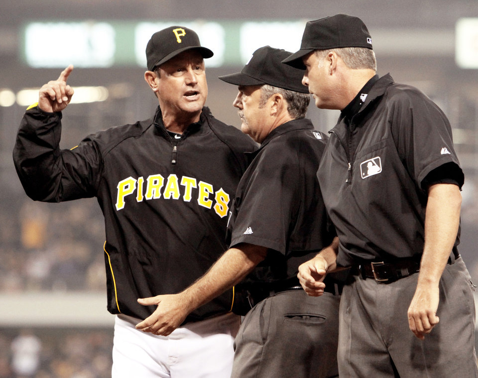 Photo - Second-base umpire Tim Tschida, center, gets between Pittsburgh Pirates manager John Russell, left, and first-base umpire Tim Timmons, right, after Timmons threw Russell out of the game after Russell argued a call on Saturday. AP photo