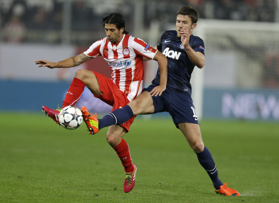 Photo - Olympiakos' Alejandro Dominguez, left, fights for the ball with Manchester United's Michael Carrick during their Champions League, round of 16, first leg soccer match at Georgios Karaiskakis stadium, in Piraeus port, near Athens, on Tuesday, Feb. 25, 2014. (AP Photo/Thanassis Stavrakis)