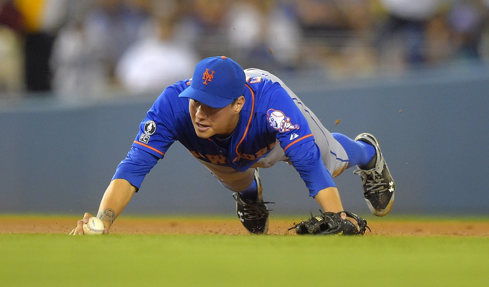 Photo - New York Mets shortstop Wilmer Flores trips while trying to throw out Los Angeles Dodgers' Yasiel Puig at first base during the fifth inning of a baseball game, Friday, Aug. 22, 2014, in Los Angeles. Puig was safe at first on the play. (AP Photo/Mark J. Terrill)