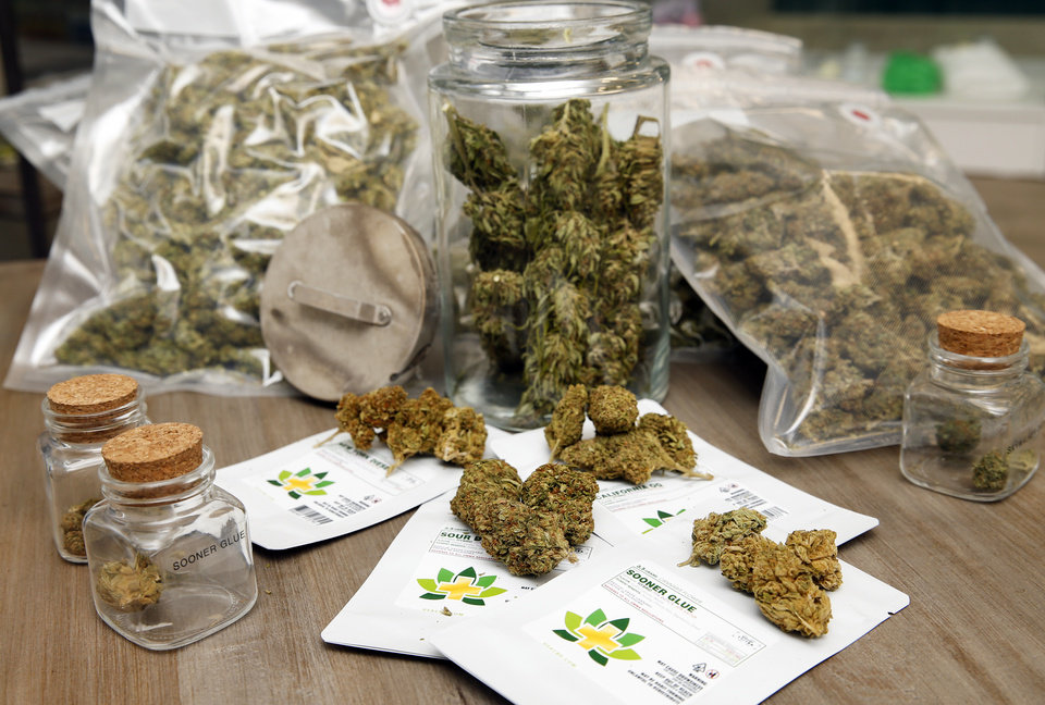Photo -  Cannabis flowers, lower center, in-store display jars and other medical marijuana products are shown at CBD Plus USA on Monday in Oklahoma City. [Photo by Nate Billings, The Oklahoman]