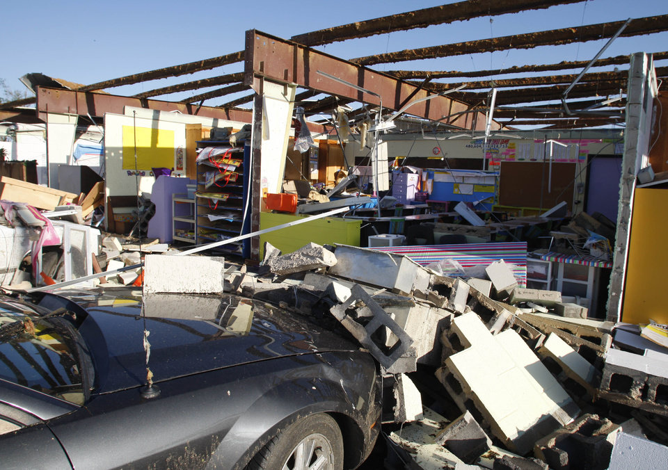 Photo - A car parked outside a school classroom is covered in rubble Friday, April 15, 2011, after a wall fell on it during Thursday night's tornado, in Tushka, Okla. (AP Photo/Sue Ogrocki)