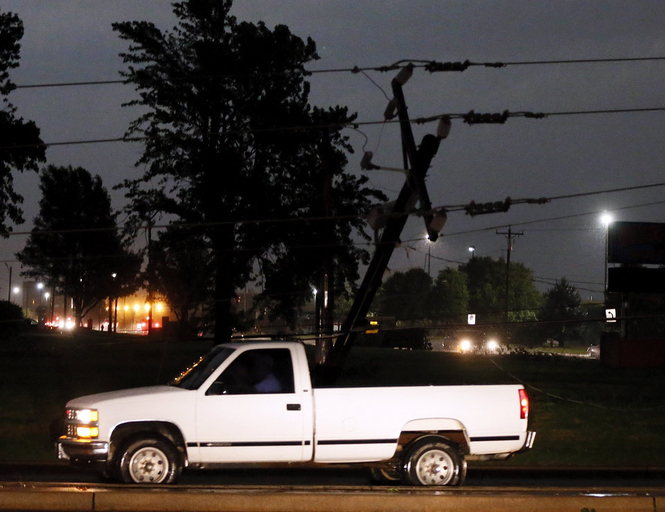 Photo - A truck drives past a silhouetted downed power pole at SW 44th and Council in Oklahoma City, Friday, May 31, 2013. Severe Thunderstorms brought tornadoes, high winds, heavy rain and hail to central Oklahoma on Friday. Photo by Nate Billings, The Oklahoman