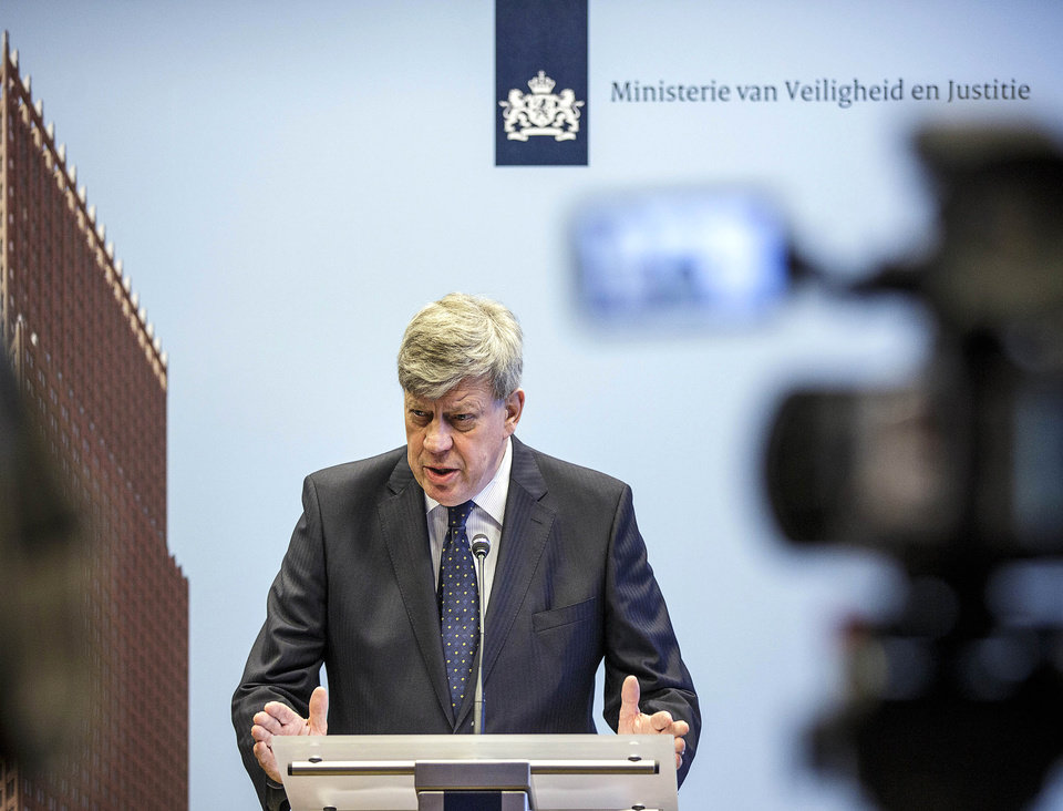 Photo - Dutch Justice Minister Ivo Opstelten gestures during a press conference at the Ministry of Security and Justice in The Hague, Netherlands, Friday, July 18, 2014. Flags are flying half-staff across the Netherlands as the country mourns at least 173 of its citizens killed when a Malaysia Airlines passenger jet was shot down in eastern Ukraine on Thursday July 17. Opstelten called the Dutch death toll of at least 173, 'an almost unbelievable number. The terrible reality of this disaster is hitting home more and more.' Opstelten told reporters it is critical to establish the exact cause of the tragedy. 'Many of our countrymen and women have died. That is why it is also important that the Netherlands, as part of an international investigative team, can begin research as soon as possible at the location where the aircraft crashed.' (AP Photo/Phil Nijhuis)