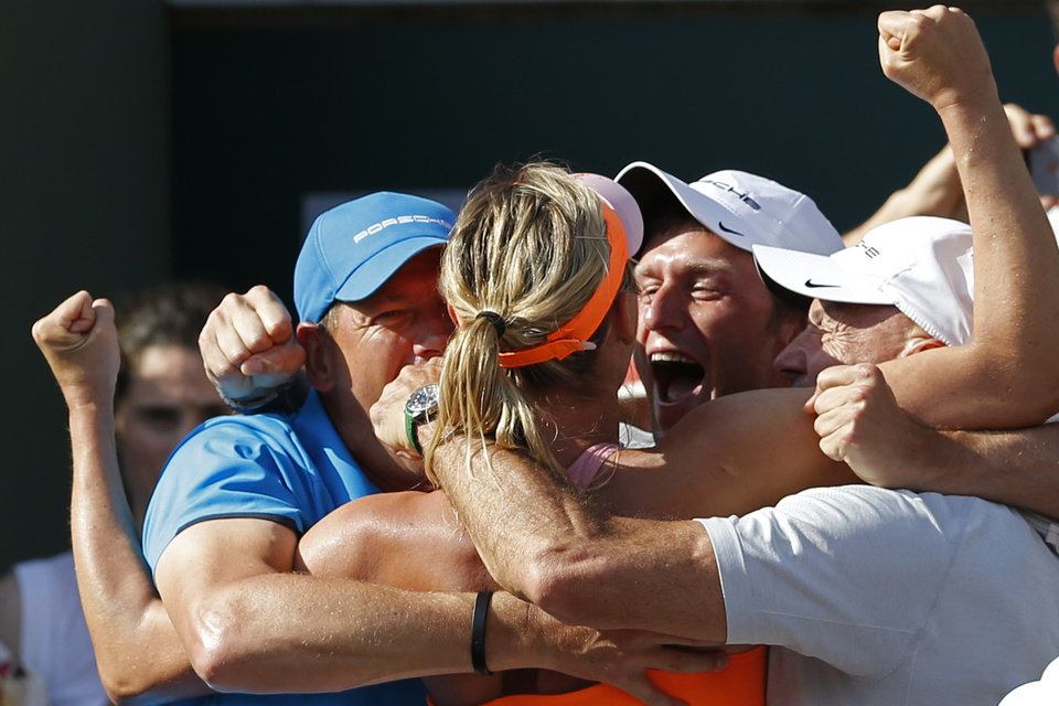 Photo - Russia's Maria Sharapova, center, celebrates with her coaches after winning the final of the French Open tennis tournament against Romania's Simona Halep at the Roland Garros stadium, in Paris, France, Saturday, June 7, 2014. Sharapova won in three sets 6-4, 6-7, 6-4. (AP Photo/Darko Vojinovic)