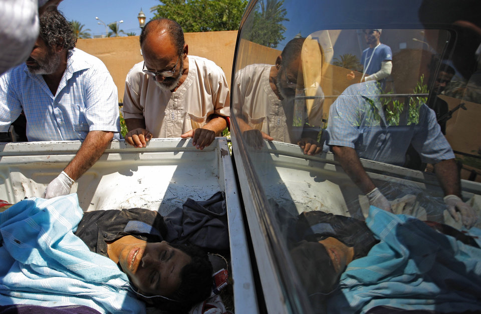 Medics check the body of killed a pro-Gadhafi fighter in the Abu-Rafat hospital on the outskirts of Zawiya, LIbya, Sunday, Aug. 21, 2011. Libyan rebels said they were less than 20 miles (30 kilometers) from Moammar Gadhafi\'s main stronghold of Tripoli on Sunday, a day after opposition fighters launched their first attack on the capital itself. Fighters said a 600-strong rebel force that set out from Zawiya has reached the outskirts of the village of Jedaim and was coming under heavy fire from regime forces on the eastern side of the town. (AP Photo/Sergey Ponomarev)