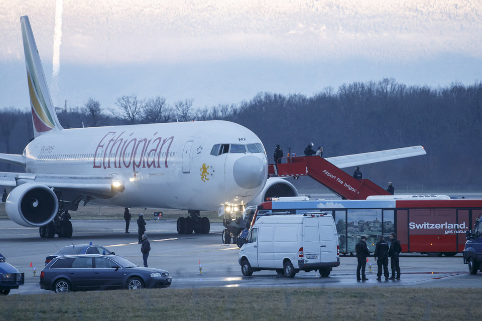 Photo - Passengers are evacuated from a hijacked Ethiopian Airlines Plane on the airport in Geneva, Switzerland, Monday, Feb. 17, 2014. A hijacked aircraft traveling from Addis Abeda, Ethiopia, to Rome, Italy, has landed at Geneva's international airport early Monday morning. Swiss authorities have arrested the hijacker. (AP Photo/Keystone, Salvatore Di Nolfi)