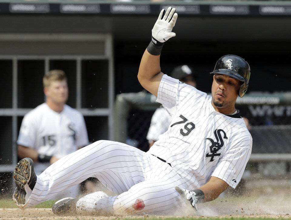Photo - Chicago White Sox's Jose Abreu scores on a fielding error by Houston Astros second baseman Jose Altuve during the sixth inning of a baseball game in Chicago on Sunday, July 20, 2014. (AP Photo/Nam Y. Huh)