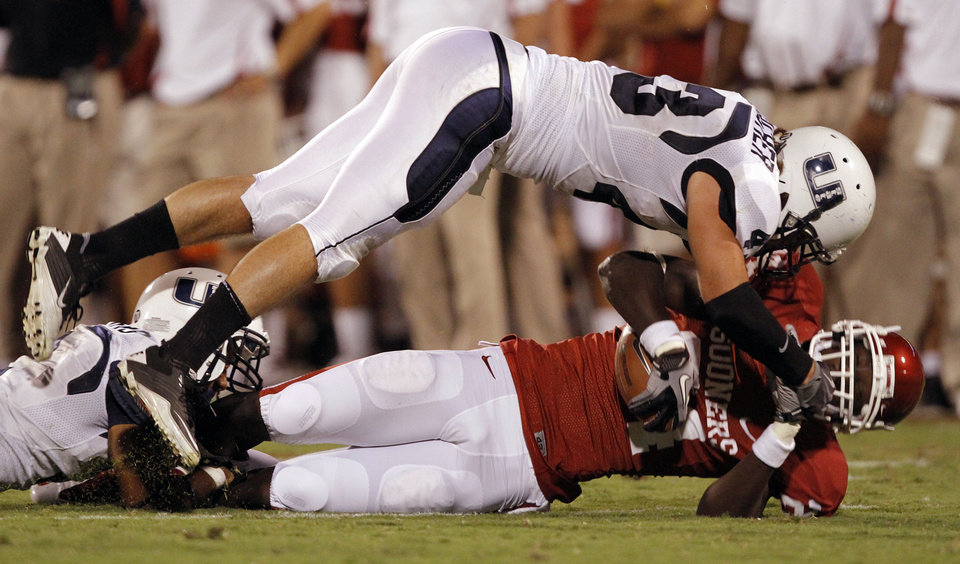 Photo - Utah State's Kyle Gallagher (43) puts a hit on Oklahoma's Dejuan Miller (24) during the second half of the college football game between the University of Oklahoma Sooners (OU) and Utah State University Aggies (USU) at the Gaylord Family-Oklahoma Memorial Stadium on Saturday, Sept. 4, 2010, in Norman, Okla.   Photo by Chris Landsberger, The Oklahoman