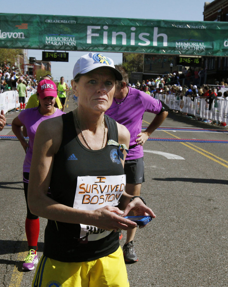 Linda McMichael, who ran in the Boston Marathon, crosses the finish line of the Oklahoma City Memorial Marathon in Oklahoma City, Sunday, April 28, 2013, By Paul Hellstern, The Oklahoman