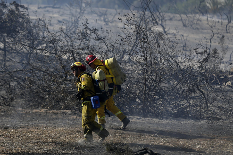 Photo - Firefighters make hike through burned vegetation during a wildfire Wednesday, May 14, 2014, in Carlsbad, Calif. Flames engulfed suburban homes and shot up along canyon ridges in one of the worst of several blazes that broke out Wednesday in Southern California during a second day of a sweltering heat wave, taxing fire crews who fear the scattered fires mark only the beginning of a long wildfire season. (AP Photo)