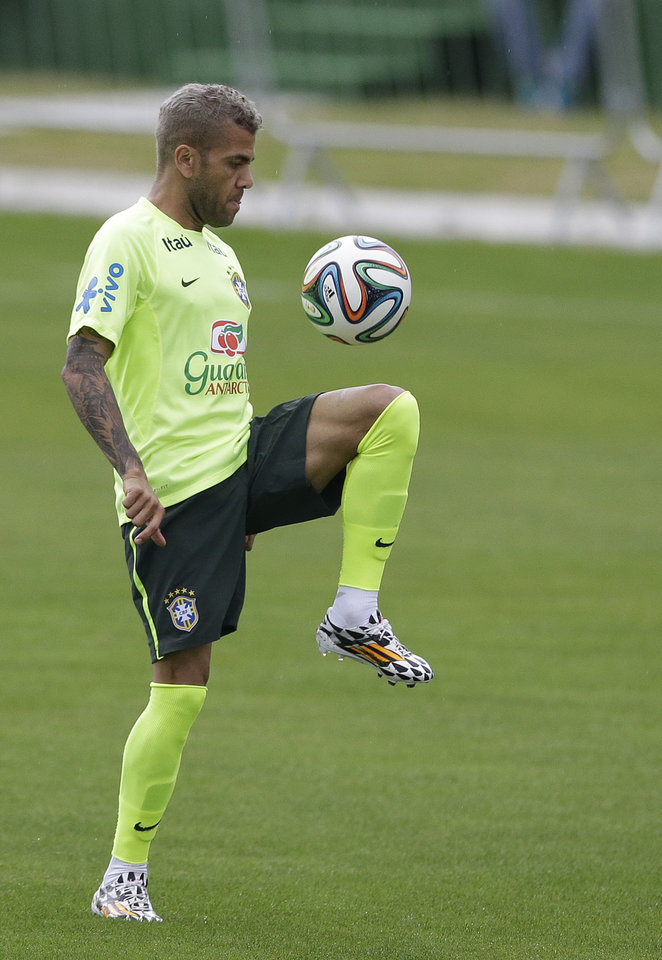 Photo - Brazil's Dani Alves juggles a ball during a training session at the Granja Comary training center in Teresopolis, Brazil, Friday, June 20, 2014. Brazil plays in group A of the 2014 soccer World Cup. (AP Photo/Andre Penner)