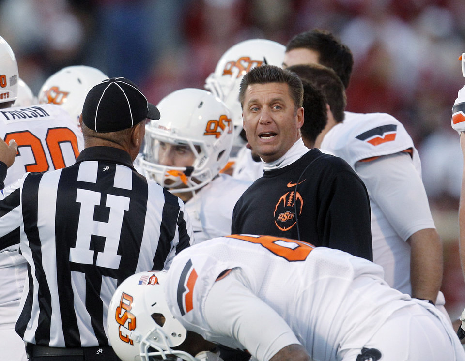 Oklahoma State coach Mike Gundy talks to an official during a timeout in the third quarter of an NCAA college football game against Oklahoma in Norman, Okla., Saturday, Nov. 24, 2012. Oklahoma won in overtime, 51-48. (AP Photo/Sue Ogrocki)