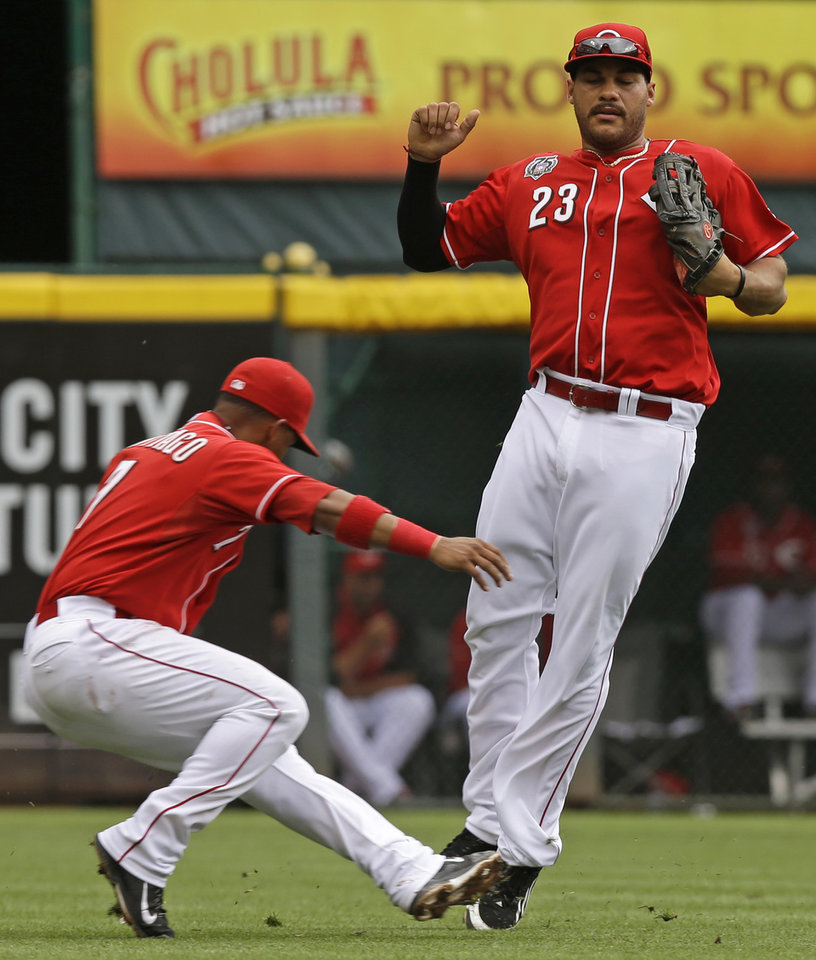 Photo - Cincinnati Reds left fielder Donald Lutz (23) avoids a collision with shortstop Ramon Santiago after Santiago caught a pop fly hit by Washington Nationals' Bryce Harper in the fourth inning of a baseball game, Sunday, July 27, 2014, in Cincinnati. (AP Photo/Al Behrman)