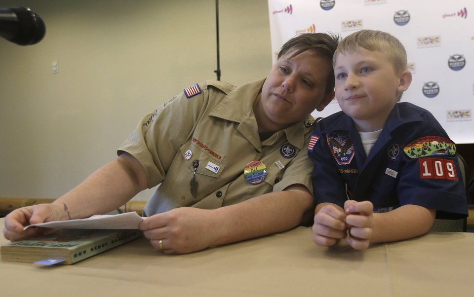 Photo - Former Boys Scout leader Jennifer Tyrrell, left, rests her head on her son and current Boy Scout Cruz Burns, 8, before an news conference at the Equal Scouting Summit being held near where the Boy Scouts of America are holding their annual meeting Wednesday, May 22, 2013, in Grapevine, Texas. Delegates to the Boys Scouts of America meeting are expected to address a proposal to allow gay scouts into the organization. (AP Photo/LM Otero)