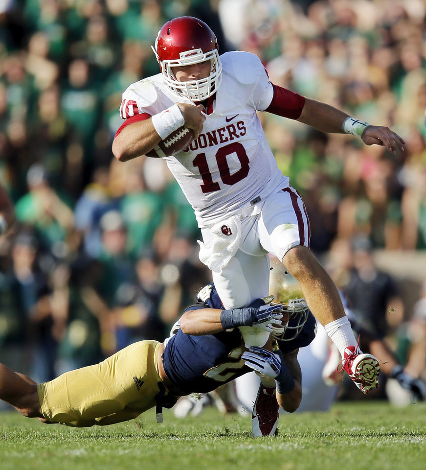 Photo - Notre Dame's Bennett Jackson (2) tries to bring down Oklahoma's Blake Bell (10) on a keeper in the second quarter during a college football game between the University of Oklahoma Sooners (OU) and the Notre Dame Fighting Irish at Notre Dame Stadium in South Bend, Ind., Saturday, Sept. 28, 2013. Photo by Nate Billings, The Oklahoman