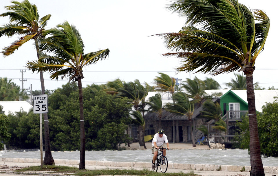 A cyclist rides his bike in Key West, Fla., Sunday, Aug. 26, 2012. Tropical Storm Isaac gained fresh muscle Sunday as it bore down on the Florida Keys, with forecasters warning it could grow into a dangerous Category 2 hurricane as it nears the northern Gulf Coast. (AP Photo/Alan Diaz) ORG XMIT: FLAD103