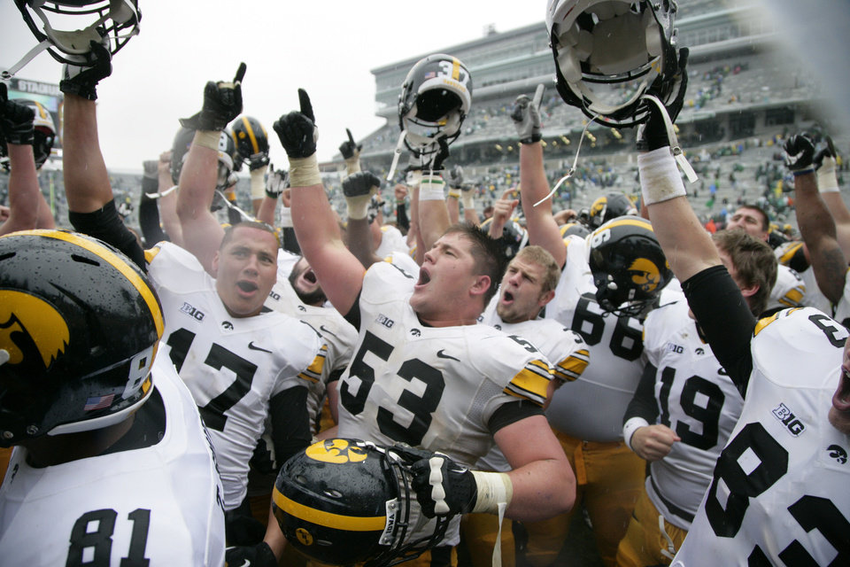 Iowa players, including Jacob Hillyer (17) and James Ferentz (53), celebrate following their 19-16 double-overtime win over Michigan State in an NCAA college football game, Saturday, Oct. 13, 2012, in East Lansing, Mich. (AP Photo/Al Goldis)