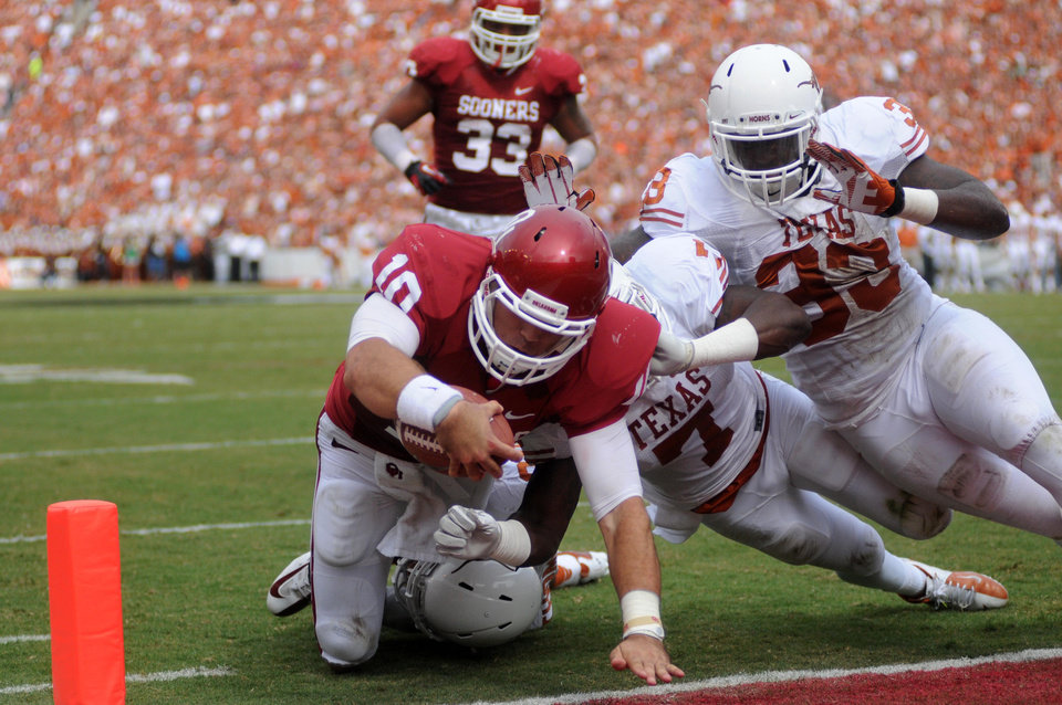 Photo -   Oklahoma quarterback Blake Bell (10) stretches for the gaol line scoring a touchdown against Texas linebacker Steve Edmond (33), defensive back Mykkele Thompson (2) and linebacker Demarco Cobbs (7) during the first half of an NCAA college football game at the Cotton Bowl Saturday, Oct. 13, 2012, in Dallas. (AP Photo/The Daily Texan, Lawrence Peart)