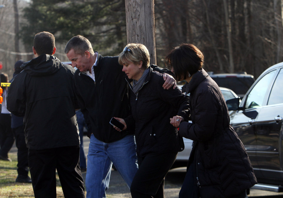 Photo - Teachers walk away from the Sandy Hook Elementary School in Newtown, Conn. following a shooting where authorities say a gunman opened fire, leaving 27 people dead, including 20 children, Friday, Dec. 14, 2012. (AP Photo/The Journal News, Frank Becerra Jr.) MANDATORY CREDIT, NYC OUT, NO SALES, TV OUT, NEWSDAY OUT; MAGS OUT ORG XMIT: NYWHI108