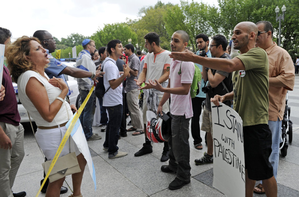 Photo - A Palestinian supporter, right, shouts at an Israeli supporter, left, during a rally near the White House in Washington, Saturday, Aug. 2, 2014. A small group of Israeli supporters were surrounded by a larger group of Palestinian supporters who were protesting against the violence in Gaza. (AP Photo/Susan Walsh)
