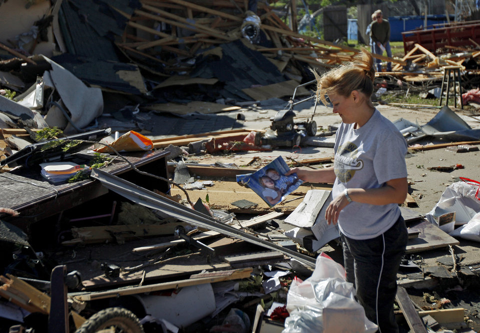 Photo - Careylyn Talley finds a photo of her children as she sorts through the debris at her law firm in Woodward, Okla., Sunday, April 15, 2012. A tornado that killed five people struck Woodward, Okla., shortly after midnight on Sunday, April 15, 2012.  Photo by Bryan Terry, The Oklahoman