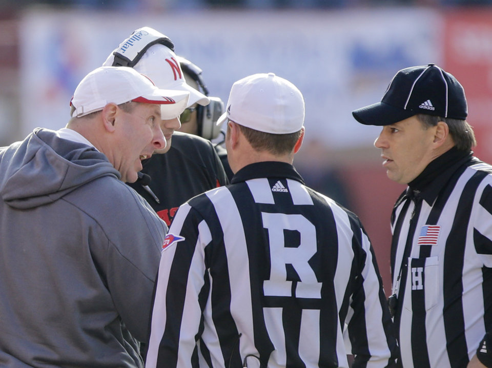 Photo - Nebraska head coach Bo Pelini, left, protests a pass interference call to referee Alex Kemp, center, and linesman Steven Matarante, right, in the third quarter of an NCAA college football game against Iowa in Lincoln, Neb., Friday, Nov. 29, 2013. Iowa won 38-17. (AP Photo/Nati Harnik)
