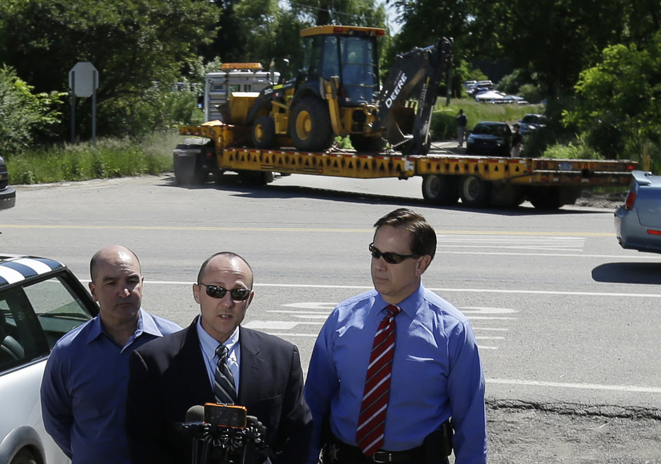 A backhoe arrives on the scene as Robert Foley, center, special agent in charge of the FBI's Detroit division, addresses the media with Oakland County Sheriff Michael Bouchard, right, in Oakland Township, Mich., Monday, June 17, 2013 where officials search for the remains of Teamsters union president Jimmy Hoffa who disappeared from a Detroit-area restaurant in 1975. (AP Photo/Carlos Osorio)