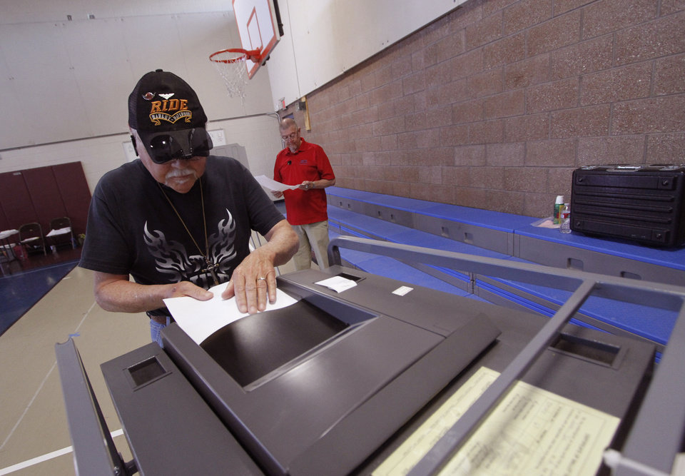 Photo - Santiago J. Lopez inserts his ballot into the tabulator at precinct 67 at Ramirez Thomas Elementary School on Tuesday, June 3, 2014 in Santa Fe, N.M.  Voting traffic at the polls for the New Mexico primary was reportedly slow Tuesday as officials prepared for a low turnout. (AP Photo/The Santa Fe New Mexican, Luis Sánchez Saturno)
