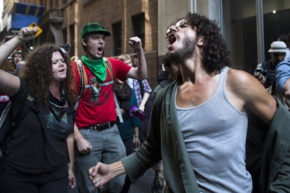 Photo -   Occupy Wall Street protestors chant during a march in the Financial District, Monday, Sept. 17, 2012, in New York. Multiple Occupy Wall Street protestors have been arrested during a march toward the New York Stock Exchange on the anniversary of the grass-roots movement. (AP Photo/John Minchillo)