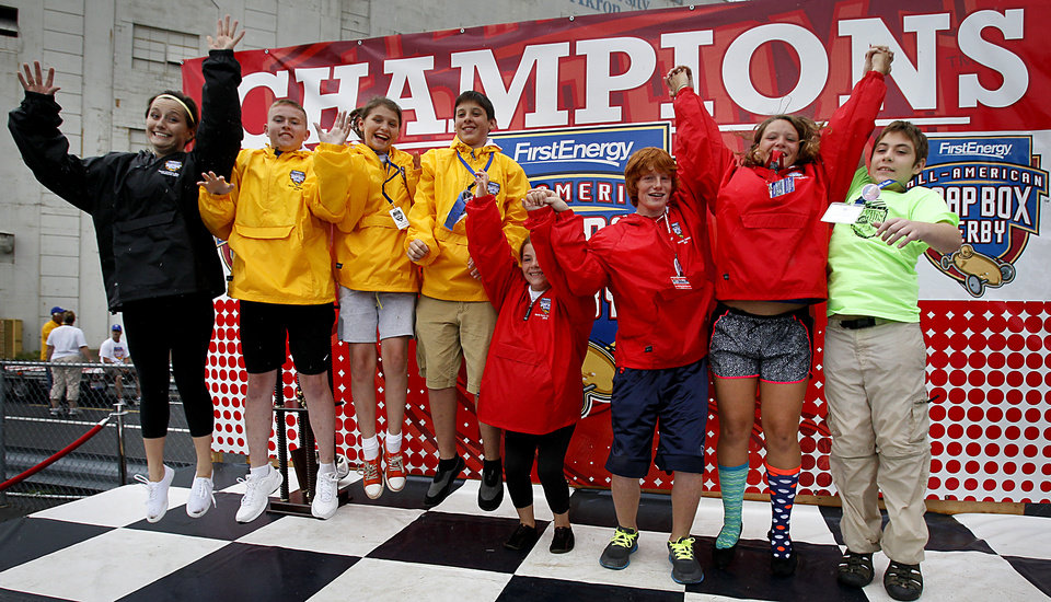 Champions Anne Taylor, left, Ultimate Speed division; Jay Warnick, Local Masters; Macaila Ziolkowski, Local Stock; Bryce Volpe, Local Super Stock; Erin Donovan, Rally Stock; Ricky Desens, Rally Super Stock; Melanie Kohout, Rally Masters; and Kyle Bolen, Super Kids, jump on stage for the media, at the 76th All-American Soap Box Derby on Saturday, July 27, 2013, in Akron, Ohio. (AP Photo/Akron Beacon Journal, Paul Tople)