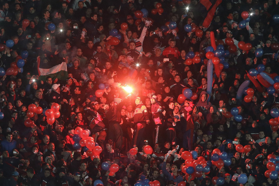 Photo - Fans of Argentina's San Lorenzo light a flare before the start of a Copa Libertadores final soccer match against Paraguay's Nacional in Buenos Aires, Argentina,  Wednesday, Aug. 13, 2014. (AP Photo/Victor R. Caivano)