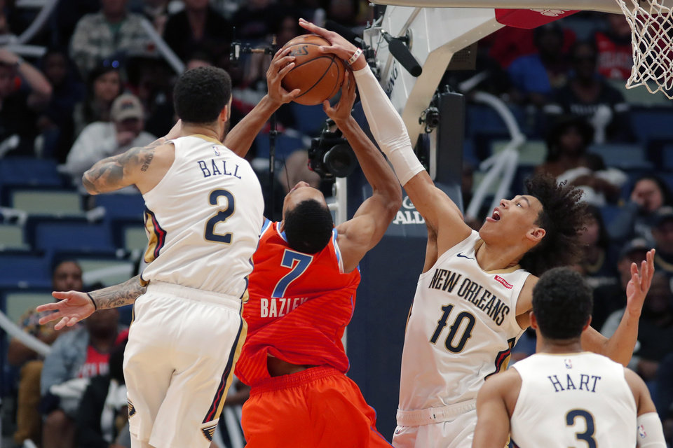 Photo - Oklahoma City Thunder forward Darius Bazley (7) is stopped as he drives to the basket between New Orleans Pelicans guard Lonzo Ball (2) and center Jaxson Hayes (10) in the second half of an NBA basketball game in New Orleans, Sunday, Dec. 1, 2019. (AP Photo/Gerald Herbert)