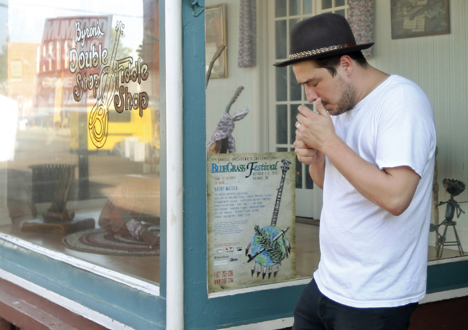 Photo - In this Sept. 5, 2013, photo Marcus Mumford, of the band Mumford & Sons, lights a cigarette as he walks out of Byron Berline's Double Stop Fiddle Shop in Guthrie,, Okla. The population of the small Oklahoma town is expected to quadruple this weekend as people come to watch the British folk rock band on the second stop of the Mumford & SonsÂ' Gentlemen of the Road concert series in Guthrie. (AP Photo/Sue Ogrocki) ORG XMIT: OKSO106