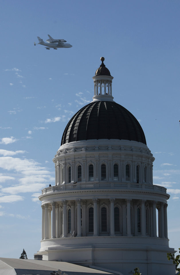 Photo -   The space shuttle Endeavour passes over the California state Capitol, Friday, Sept. 21, 2012, in Sacramento, Calif. Endeavour is making a final trek across the country to the California Science Center in Los Angeles, where it will be permanently displayed.(AP Photo/Rich Pedroncelli)