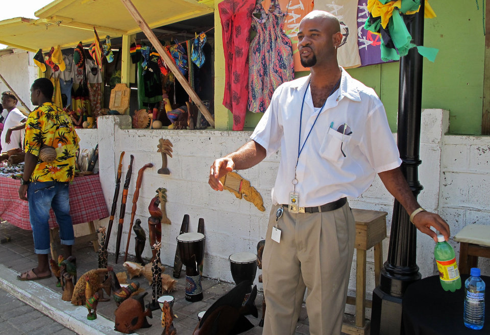 In this Sept. 26, 2012 photo, street vendor Paul Davy sells wooden statues to tourists who disembarked from the Royal Caribbean's Allure of the Seas cruise ship in Falmouth, northern Jamaica. Trade groups say the flourishing cruise ship industry injects about $2 billion a year into the economies of the Caribbean, the world�s No. 1 cruise destination, but critics complain that it produces relatively little local revenue because so many passengers dine, shop and purchase heavily marked-up shore excursions on the boats or splurge at international chain shops on the piers. (AP Photo/David McFadden)