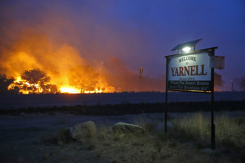 Photo - A wildfire burns homes in Yarnell, Ariz. on Sunday, June 30, 2013. An Arizona fire chief says the wildfire that killed 19 members of his crew near the town was moving fast and fueled by hot, dry conditions. The fire started with a lightning strike on Friday and spread to 2,000 acres on Sunday amid triple-digit temperatures. (AP Photo/The Arizona Republic, David Kadlubowski)