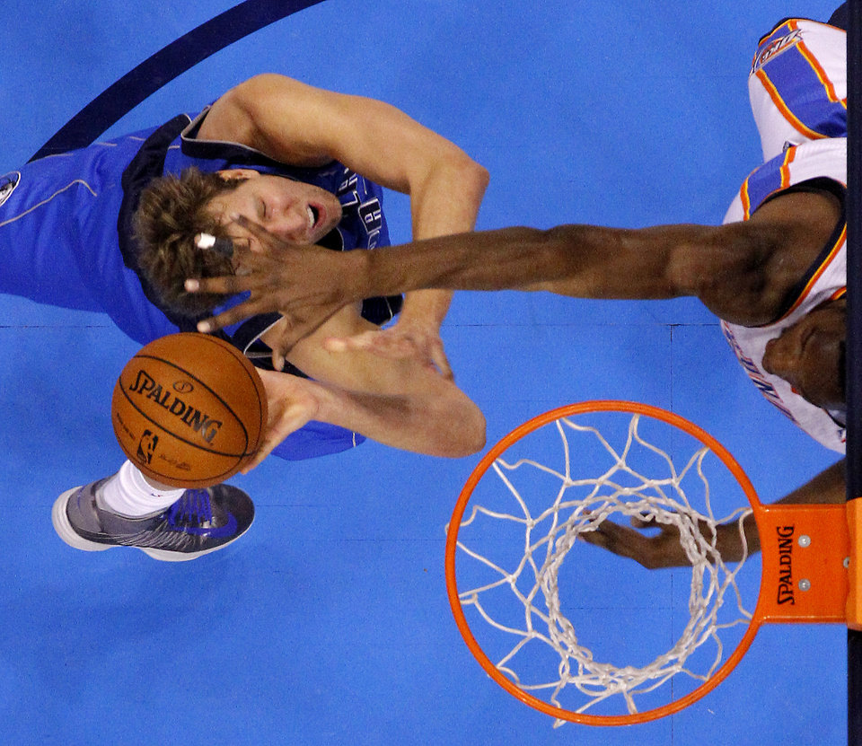 Photo - Oklahoma City's Hasheem Thabeet (34) defends Dallas' Dirk Nowitzki (41) during an NBA basketball game between the Oklahoma City Thunder and the Dallas Mavericks at Chesapeake Energy Arena in Oklahoma City, Thursday, Dec. 27, 2012.  Oklahoma City won 111-105. Photo by Bryan Terry, The Oklahoman