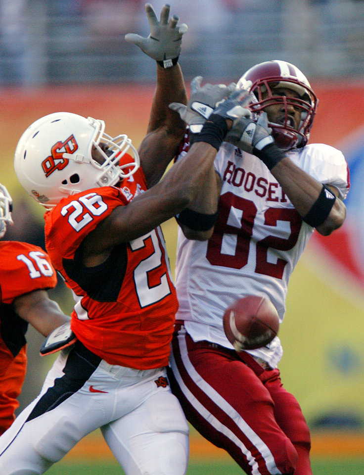 Photo - Oklahoma State's Quinton Moore (26) breaks up a pass for Indiana's James Hardy (82) during the first half of the Insight Bowl college football game between Oklahoma State University (OSU) and the Indiana University Hoosiers (IU) at Sun Devil Stadium on Monday, Dec. 31, 2007, in Tempe, Ariz. 