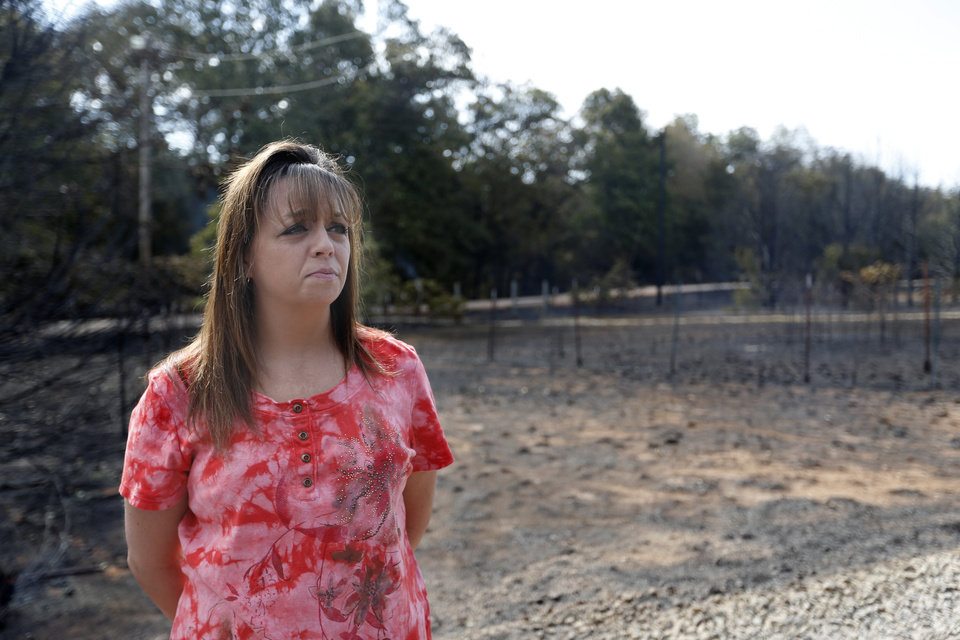 Photo - Laurilyn Harris surveys the damage at her cousin's home, Sunday, Aug. 5, 2012, in Glencoe, Okla., after wildfires moved through the area Saturday.