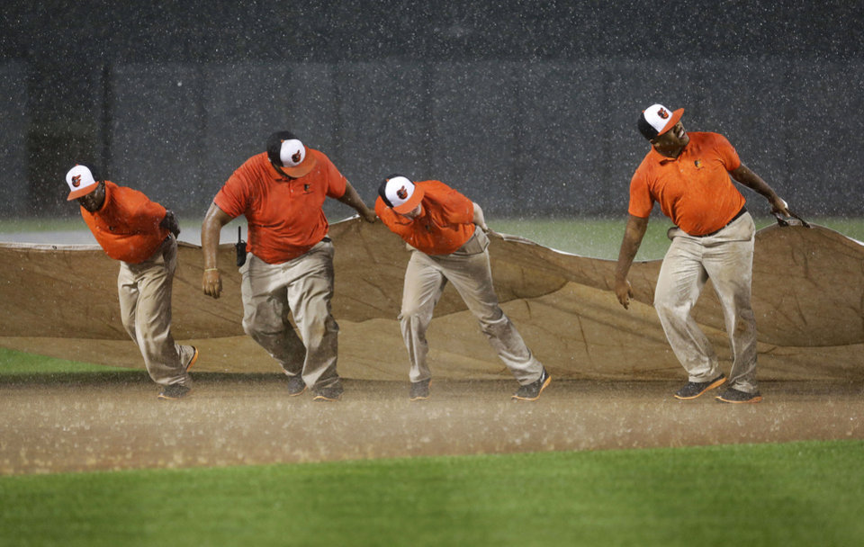 Photo - Members of the Baltimore Orioles grounds crew struggle to pull a tarp over the infield as heavy rain falls in the first inning of an interleague baseball game between the Orioles and the Cincinnati Reds, Tuesday, Sept. 2, 2014, in Baltimore. (AP Photo/Patrick Semansky)