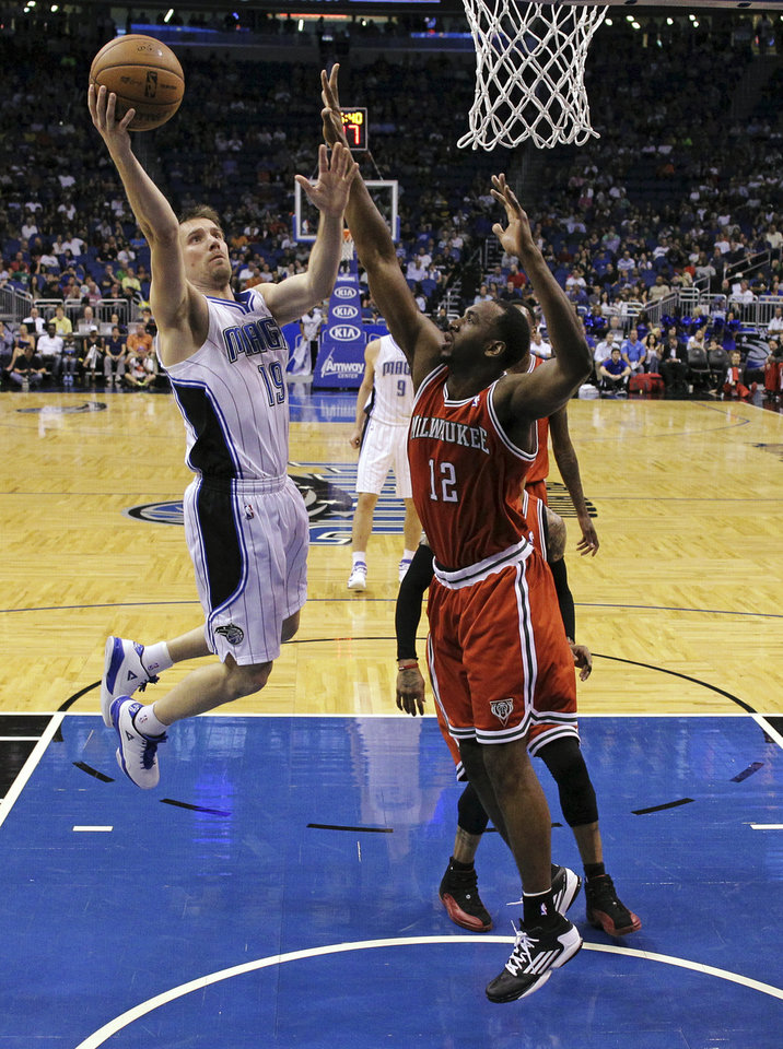 Photo - Orlando Magic's Beno Udrih (19), of Slovenia, shoots over Milwaukee Bucks' Luc Richard Mbah a Moute (12), of Cameroon, during the first half of an NBA basketball game, Wednesday, April 10, 2013, in Orlando, Fla. (AP Photo/John Raoux)