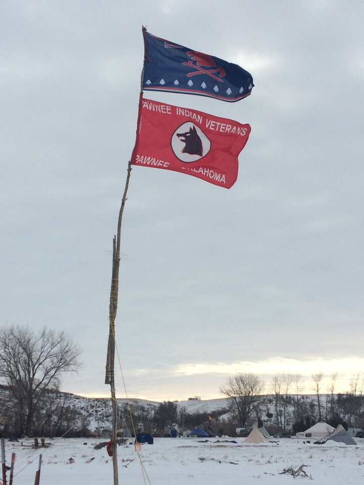 Photo -  A Pawnee flag flies in the freezing winds at the Oceti Sakowin Camp on the Standing Rock Indian Reservation. [Photo by Graham Lee Brewer, The Oklahoman]