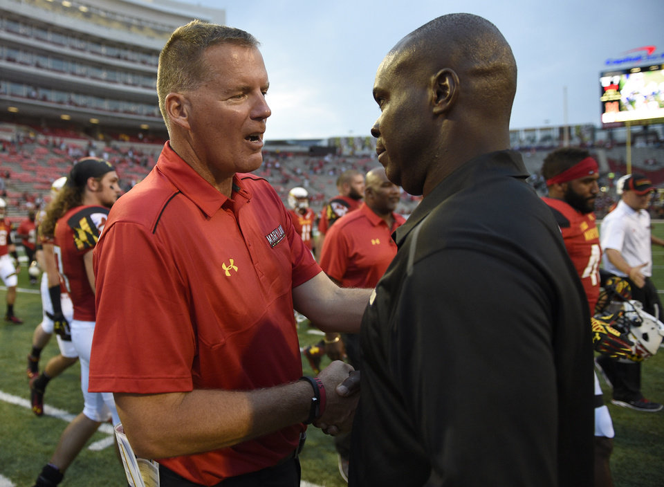 Photo - Maryland head coach Randy Edsall, left, shakes hands with James Madison head coach Everett Withers, right, after an NCAA football game, Saturday, Aug. 30, 2014, in College Park, Md. Maryland won 52-7. (AP Photo/Nick Wass)